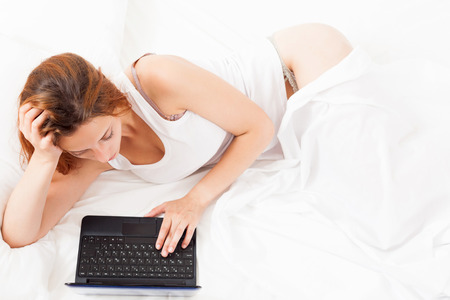 pretty  woman awaking with laptop  on her bed photo