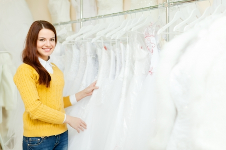 Smiling pretty bride chooses wedding outfit at shop of wedding fashion photo