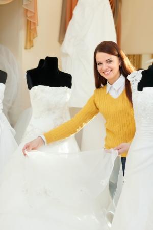 bridal salon: Smiling pretty bride chooses bridal gown in wedding boutique Stock Photo