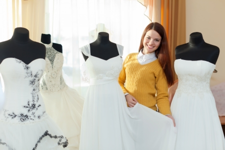Smiling woman chooses wedding outfit in bridal boutique photo
