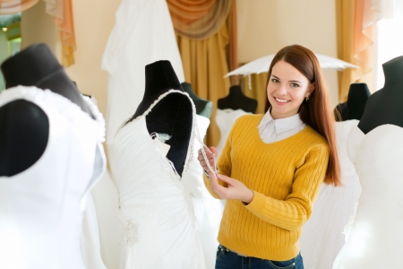 bridal gown: Smiling woman chooses bridal gown in wedding boutique