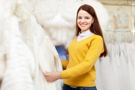 Bride shopping for wedding outfit in bridal boutique photo