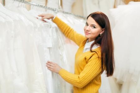 bridal gown: novia bonita elige vestido de novia en el sal�n de bodas Foto de archivo