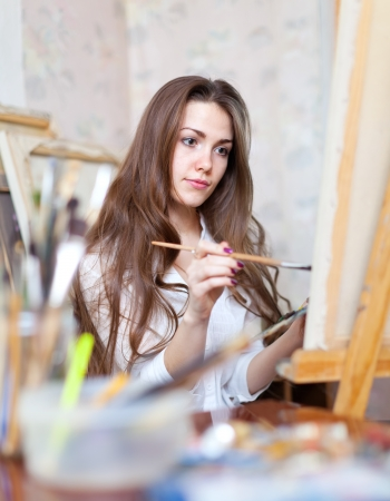 Long-haired girl paints with brushes in workshop photo