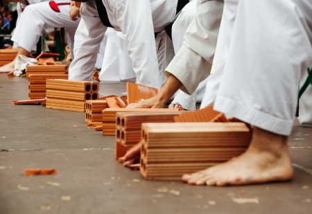 Karate students show their skills by breaking bricks photo