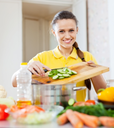 Portrait of  happy woman cooking  vegetables at domestic kitchen    photo