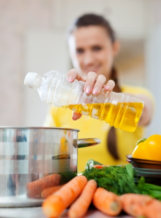 Woman pouring oil from bottle into the saucepan. Focus on hand photo