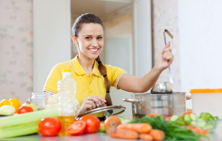 Happy beautiful woman cooking  in saucepan at home kitchen    photo