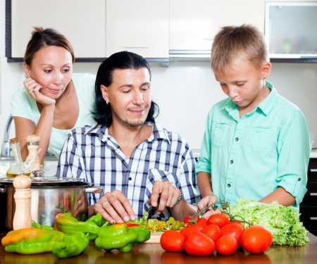 Happy family with teenager son cooking lunch with fresh vegetables at home kitchen photo