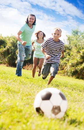 Happy adult couple and teenager playing with soccer ball at summer park photo