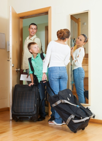 couple with teenage son with luggage near door photo