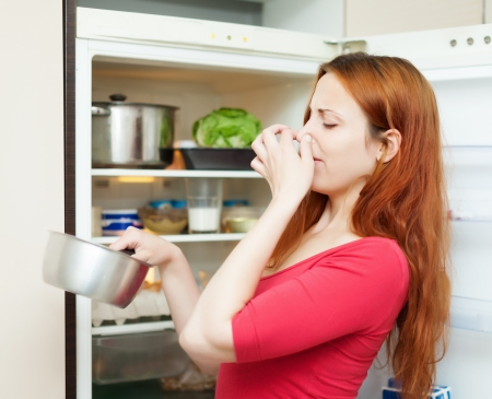 young woman in red  holding her nose because of bad smell from food near refrigerator  at home photo