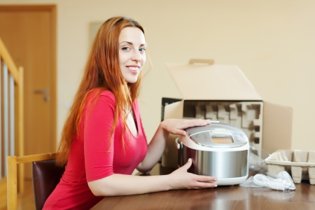 Happy young woman with new multicooker in home interior photo