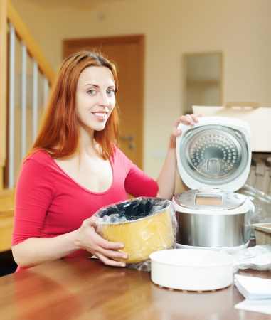 Young woman with electric slo-cooker at home photo