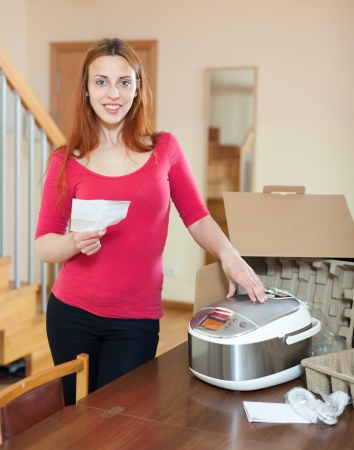 Cheerful woman unpacking and reading user manual for new crock-pot  photo
