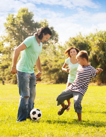 Happy parents with teenage son playing with soccer ball at summer park photo