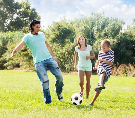women playing soccer: Middle-aged couple and teenager son playing with soccer ball  at summer park  Stock Photo
