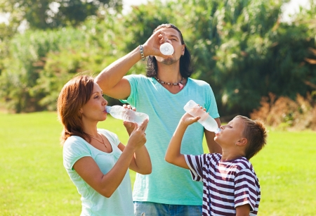 parents with teenager drinking water from plastic bottles in summer park photo