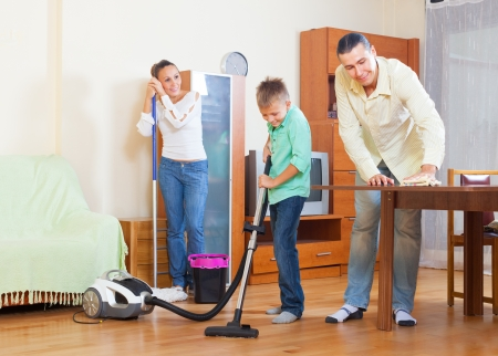 dusting: Middle-aged couple with teenage son dusting together