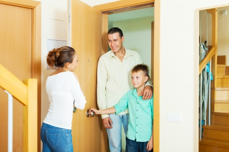 woman meeting man and boy in the doorway at home photo