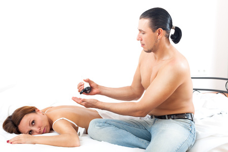 Man  massaging back of his wife in bedroom interior photo