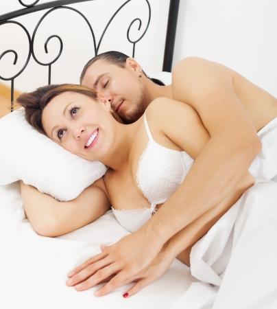 Loving middle-aged couple awaking together in bed at home photo