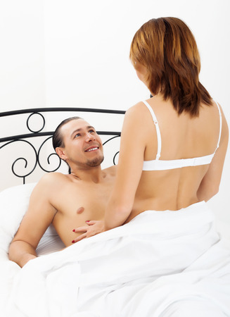 Middle-aged man and woman having sex on white sheet in bed   photo