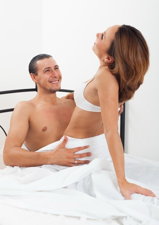 Adult man with wife having sex on bed in home interior photo