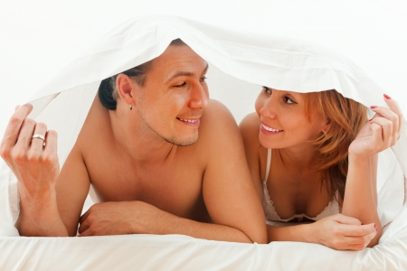 couple lying together in bed at home photo