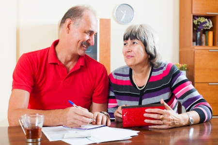 Happy mature couple with financial documents   in home   photo