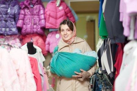 Happy woman with baby in ringsling chooses clothes at shop photo