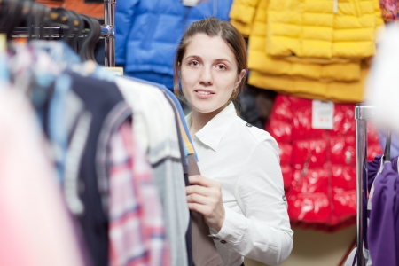 Young female buyer at clothing shop photo