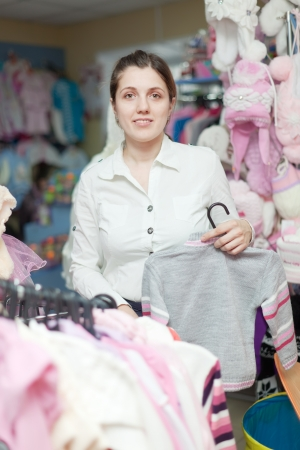 children's wear:  mother  chooses clothes for daughter at childrens wear store Stock Photo