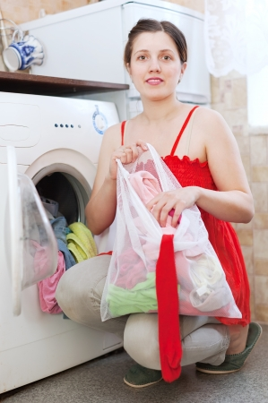 Young woman in red using bag for laundry at her home photo