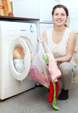 Happy housewife in white with laundry bag  near washing machine  photo