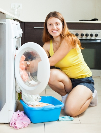 Home laundry. Smiling long-haired girl using washing machine at home photo