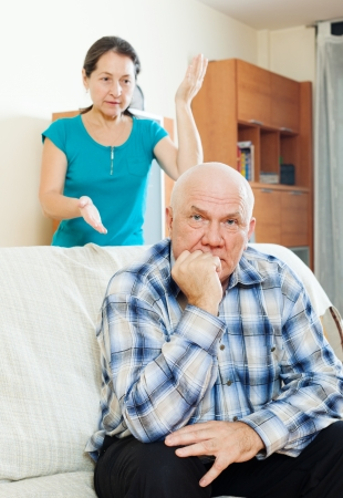 Family quarrel. Upset mature man against wife at home photo