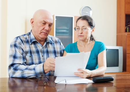 woman serious: serious mature man with wife reading financial documents