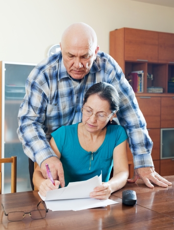 serious senior couple fills in questionnaire together at home interior photo
