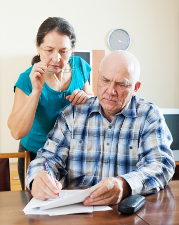 wistful mature couple reading financial documents in home  photo