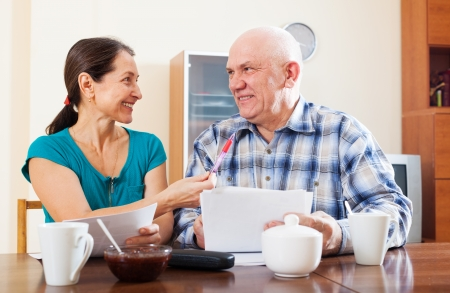utility payments: Joyful mature couple with documents at home interior