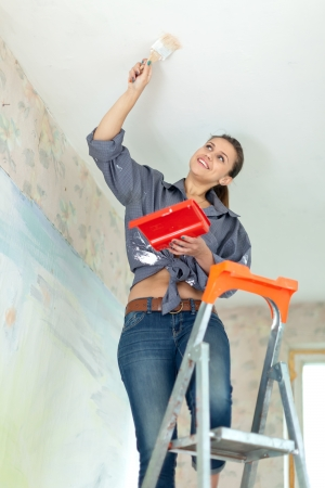 Woman paints ceiling with brush at home photo