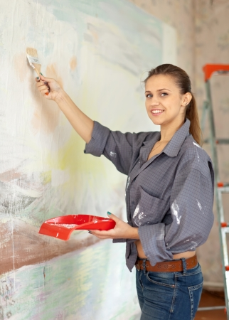 Happy woman paints wall with brush Stock Photo