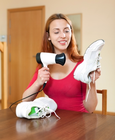 hairdryer: Happy woman warming shoes with hairdryer