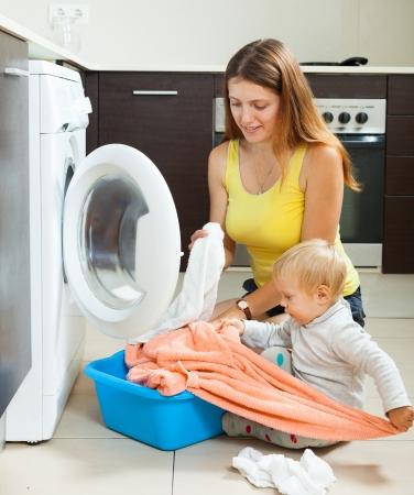 세탁기: 집에 세탁기에 옷을 넣어 가족 여성