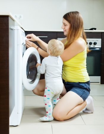 Woman with toddler using washing machine at home photo