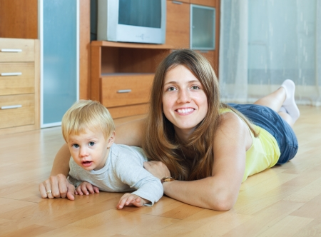 floo: happy long-haired mother and child on wooden floo