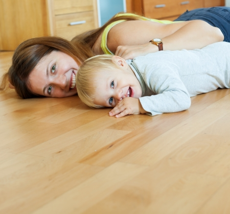 happy mom and child on wooden floor in home  photo
