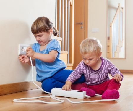 Two children  playing with electrical extension and outlet Reklamní fotografie - 24123840
