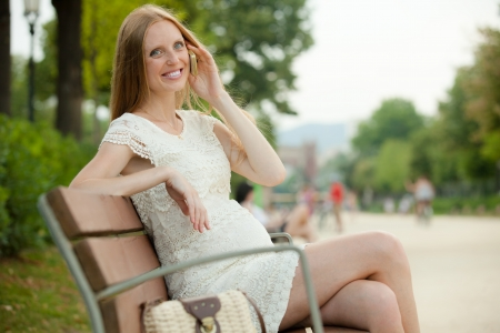 gravida: Smiling pregnant woman relaxing on bench and talking by phone in  summer park
